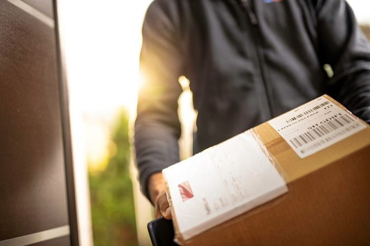A delivery man holds a box
