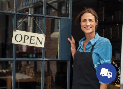 Women standing in front of store door with open sign