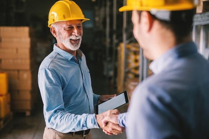 Men shake hands in warehouse